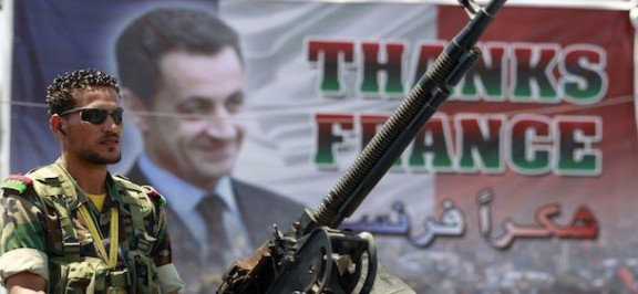 A rebel fighter mans an anti-aircraft machine gun atop a pick-up truck in front of a poster of France's President Nicolas Sarkozy in Benghazi